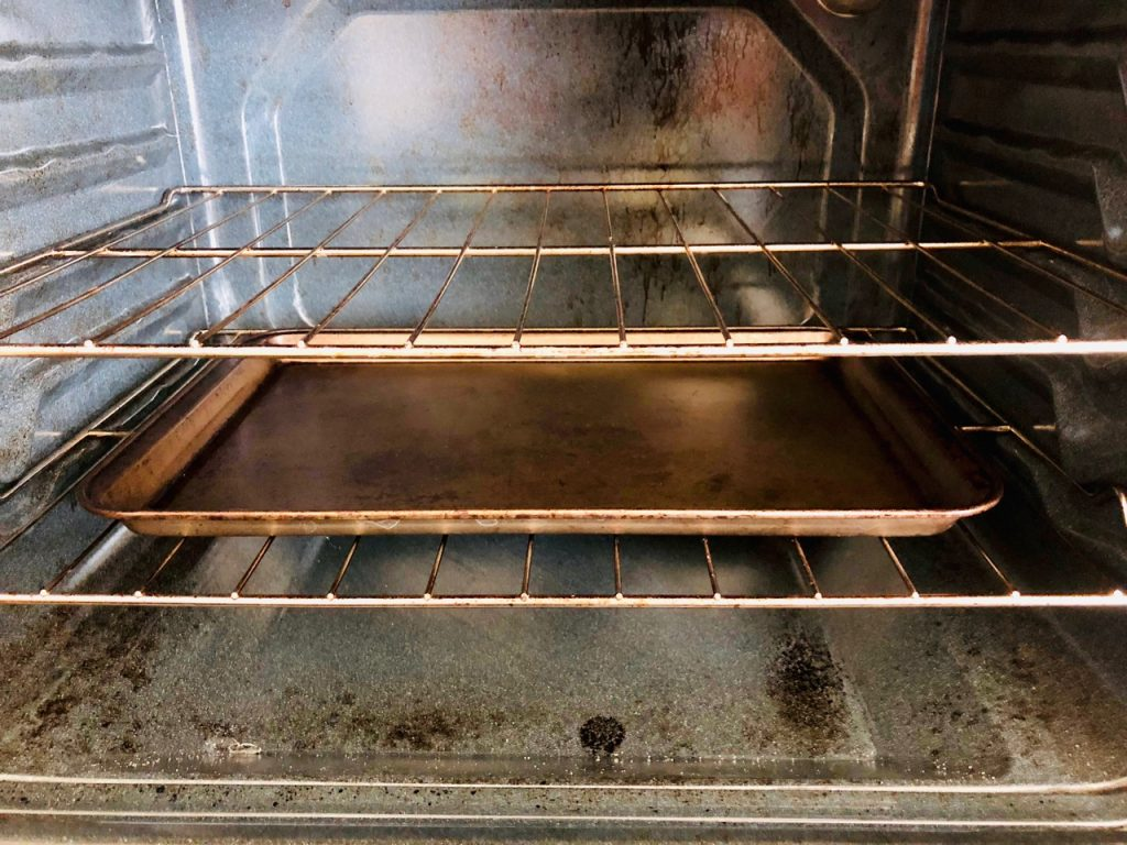 Open oven with baking pan on bottom rack