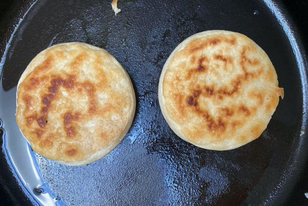 Sourdough crumpets frying on the second side.